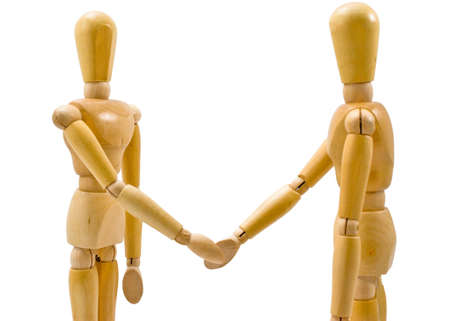 Two wooden figures shaking hands in agreement