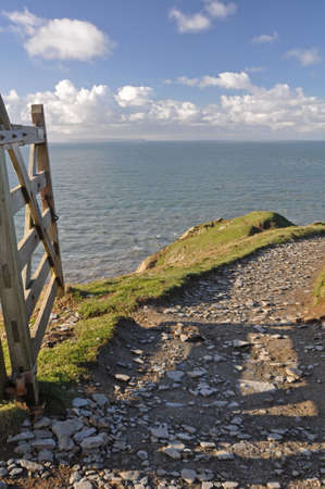 headland: Southwest Coast footpath at Baggy Point headland, Croyde, North Devon, England, a popular walk throughout the year, ths Island of Lundy is visible on the horizon Stock Photo
