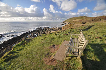 headland: Seat on the southwest coast path, near Croyde village looking towards Baggy Point headland,North Devon, England Stock Photo