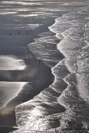surfers: Surfers on the wide expanse of Saunton Sands in North Devon, England
