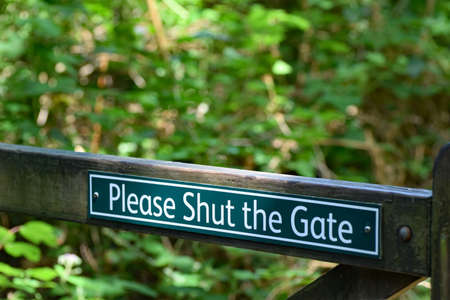 A polite, Please shut the gate sign, on a forest public footpath in North Devon, England. Stock Photo