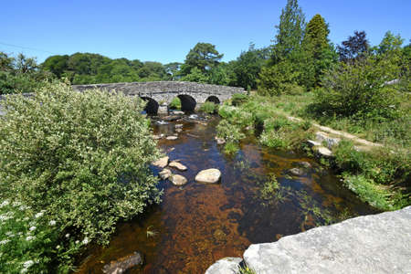 The road bridge at Postbridge, Dartmoor, England, The road ( B3212 ) runs across the open moor from Mortenhamstead to Princetown. It is viewed from the muct older granite Clapper Bridge at Postbridge.