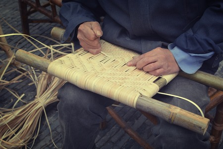 handloom: weaving from bamboo outside by old people on the knee