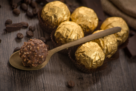 ferrero: Italian chocolate sweets Ferrero Rocher with decoration on the wooden table Stock Photo