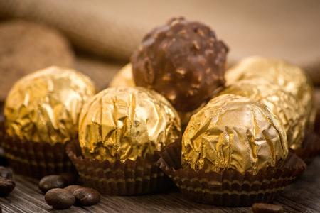 ferrero: Italian chocolate sweets Ferrero Rocher with decoration on the wooden table Stock Photo