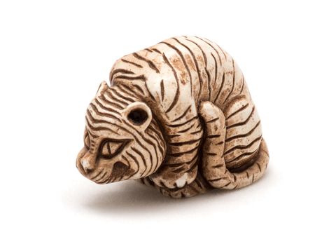Small Japanese accessory of a seated tiger. A miniature sculpture, which was used as a button-like trinket in traditional Japanese clothes kimono kosode, which was devoid of pockets.