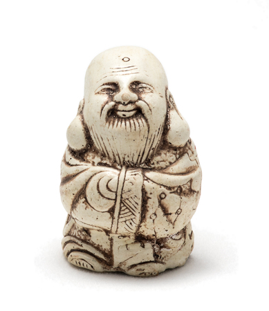 Netsuke of a satisfied man in a dressing gown. Isolated. A miniature sculpture, which was used as a button-like trinket in traditional Japanese clothes kimono kosode, which was devoid of pockets.