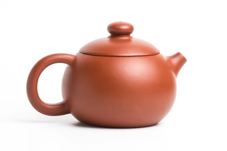 Brown small earthenware teapot with closed lid isolated on white background Stock Photo