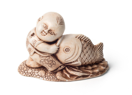Netsuke of the boy with big fish. Isolated. A miniature sculpture, which was used as a button-like trinket in traditional Japanese clothes kimono kosode, which was devoid of pockets. Stock Photo