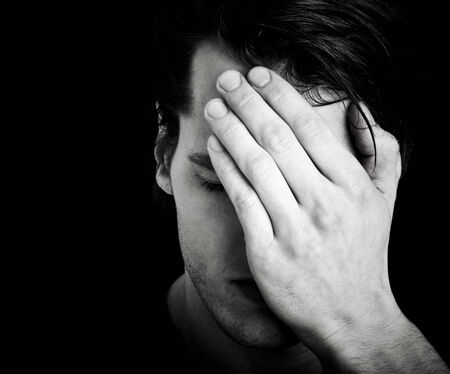 sad young man with hands before face and dark background photo