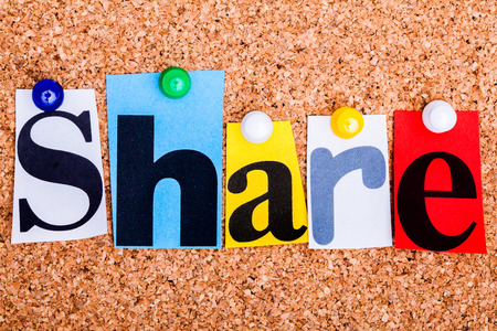 The word Share in cut out magazine letters pinned to a cork notice board photo
