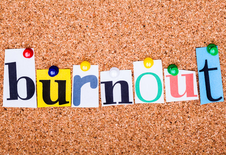 The word Burnout in cut out magazine letters pinned to a cork notice board with push pins Standard-Bild