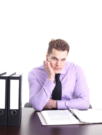 buisinessman: worried young buisinessman at his desk, isolated on white