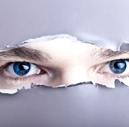 Eyes looking trough ripped paper photo