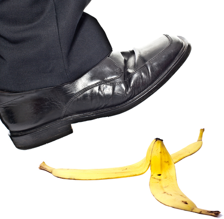 Closeup portrait of a business man foot stepping on banana peel