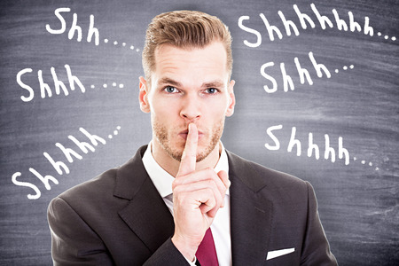 Businessman with finger on lips asking for silence photo
