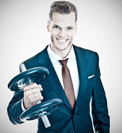 Motivation Concept - Young businessman lifting dumbbell Standard-Bild