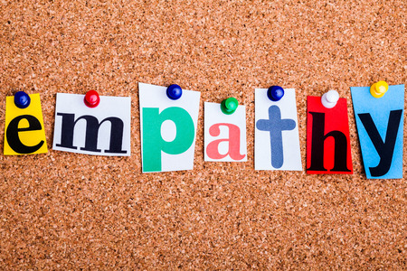 The word empathy in cut out magazine letters pinned to a cork notice board