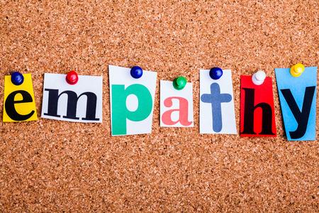 empatia: La palabra empatía en letras recortadas de revistas cubrió a un tablón de corcho Foto de archivo