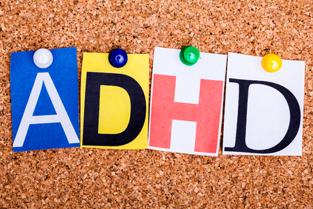hyperactivity: ADHD , abbreviation for Attention Deficit Hyperactivity Disorder in cut out magazine letters pinned to a cork notice board