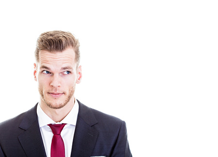 Portrait of handsome young businessman looking sideways in suit, isolated on white.