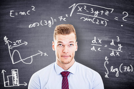 thinking young man against desk with formulas photo
