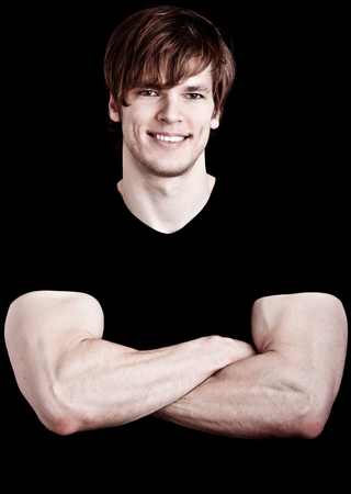 Fitness instructor with arms crossed, isolated on black photo