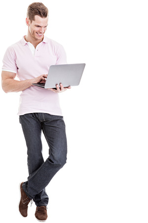 Casual young man working on laptop isolated photo