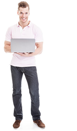 Casual young man with laptop standing isolated photo