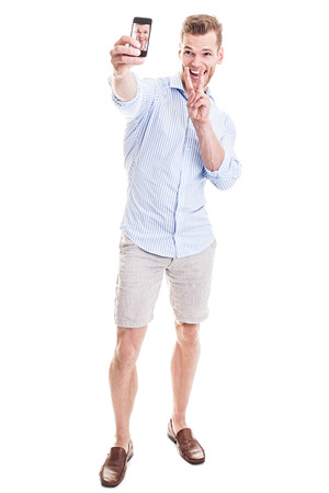 Full length portrait of a happy young man showing a peace sign and taking a SELFIE - isolated on white Stock Photo