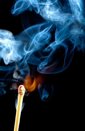 Ignition of match with smoke, isolated on black background photo