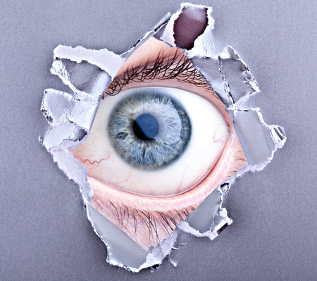 scary eye looking trough ripped paper photo
