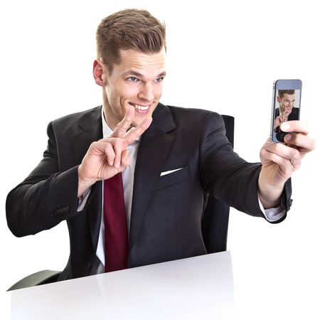 Handsome young businessman taking a selfie with his smartphone photo