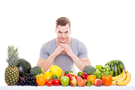 He knows whats good for you! - Handsome muscular man sitting behind a row of fruits and vegetables, isolated on white background Banco de Imagens