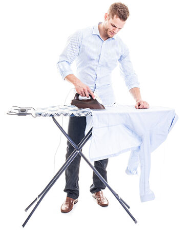 Happy young man ironing on a ironing board, isolated on white background