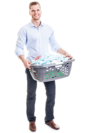 Cheerful young man holding a basket with laundry - isolated on white photo