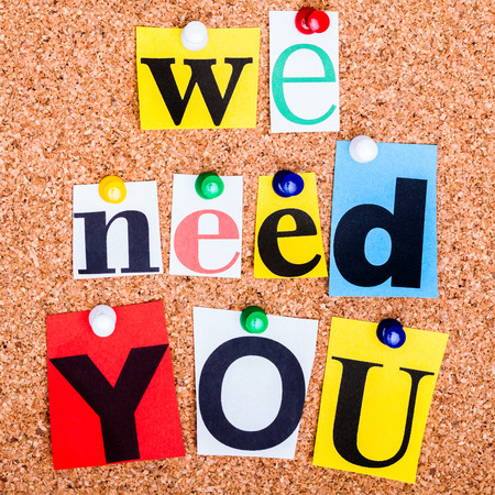 job recruitment: The phrase we need you in cut out magazine letters pinned to a cork notice board