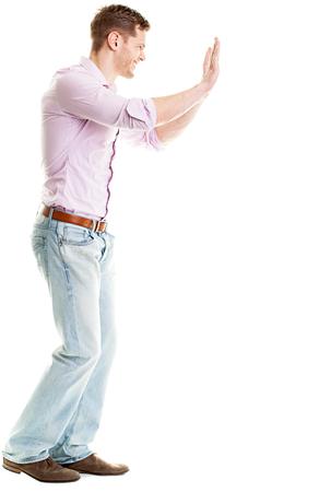Full length portret van man duwen iets geïsoleerd op een witte achtergrond