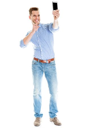 Selfie Photo - Full length portrait of a young man taking a selfie with his smart phone, isolated on white background
