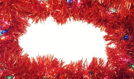 Christmas Tinsel Garland With Lights on White Background.  Happy Holidays and Season's Greetings Border Frame.