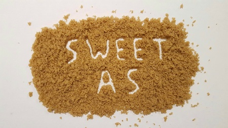 Sweet As Spelled Out in Brown Sugar on White Background.  Sweet As Sugar.