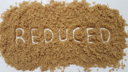 Reduced Spelled Out in Brown Sugar on White Background. Reduced Sugar.