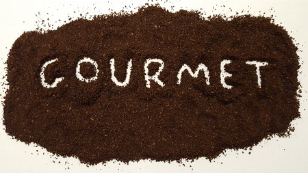 Gourmet Spelled Out in Ground Coffee on White Background.  Gourmet Coffee. Stock Photo