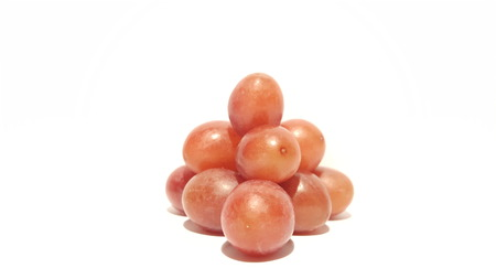 Red Grapes Stacked Into a Pyramid on White Background.  Grape Bunch/Collection.