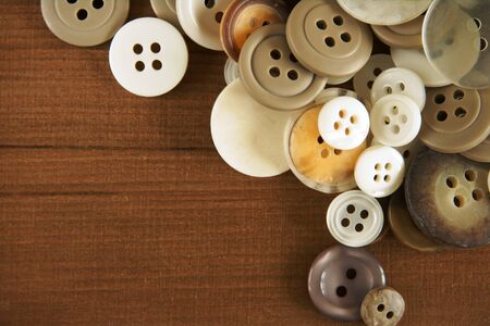 Stack of old fashioned brown beige and white buttons on a wooden background photo