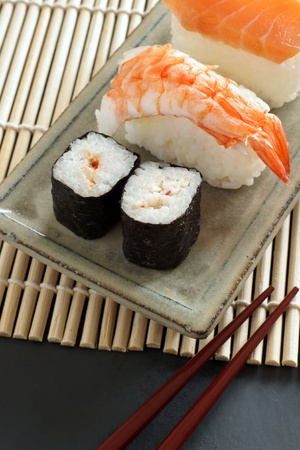 laquered: Maki sushi   nigiri sushi made with salmon and prawn on a Japanese ceramic dish with laquered chopsticks Stock Photo