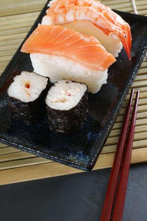 Maki sushi   nigiri sushi made with salmon and prawn on a Japanese ceramic dish with laquered chopsticks Stock Photo