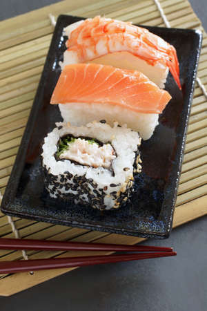laquered: Uramaki   nigiri sushi made with salmon and prawn on a Japanese ceramic dish with laquered chopsticks
