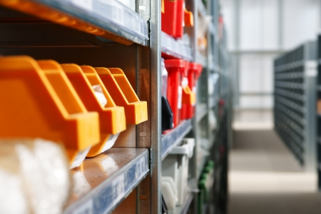 storage box: Storage bins and racks in a warehouse   Selective focus on third storage bin Stock Photo