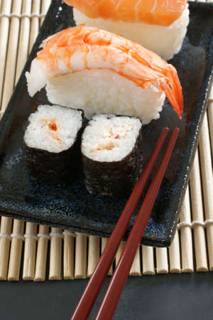 Maki sushi   nigiri sushi made with salmon and prawn on a Japanese ceramic dish with laquered chopsticks photo
